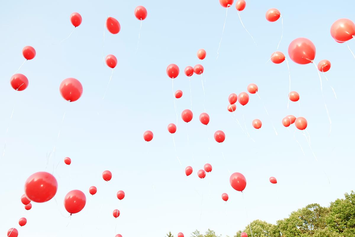 fliegende aufsteigende rote Luftballons zum Himmel auf einer Hochzeitsfeier