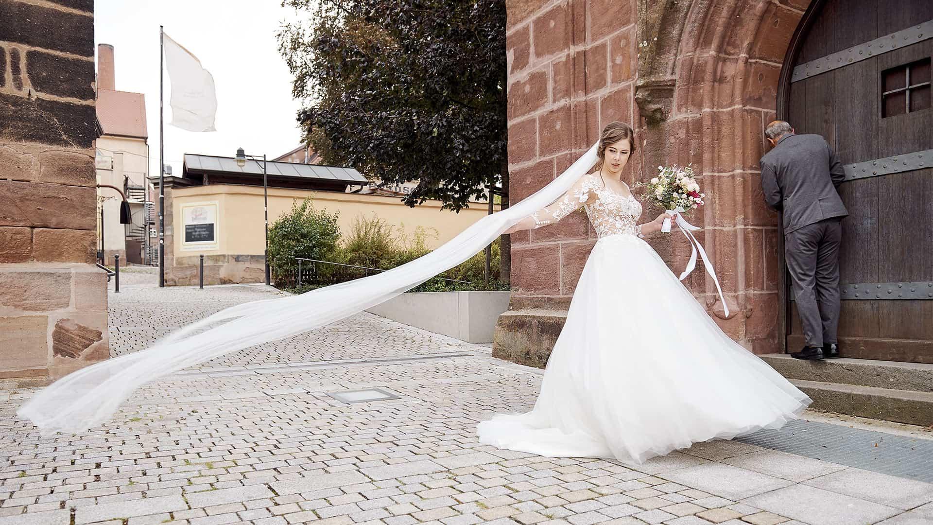 Braut steht vor der St. Rochus Kirche in Zirndorf mit wehendem Schleier